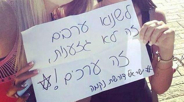 """Due ragazze reggono il foglio con la scritta """"Odiare gli arabi non è razzismo, è un valore."""" (Foto da Il popolo di Israele chiede vendetta/Facebook via)"""